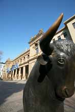 Bull in front of the stock exchange building (portrait)